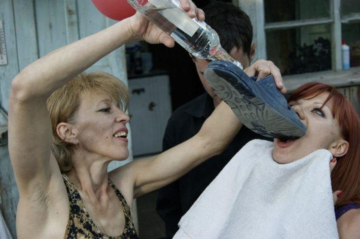 señora dando alcohol a otra mujer por medio de un zapato