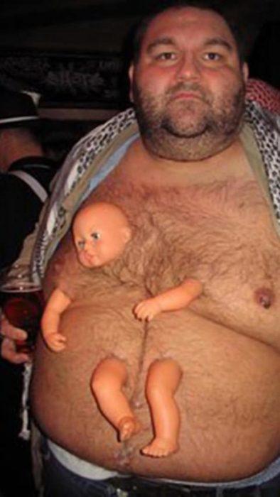señor con un bebé de plástico pegado a la panza