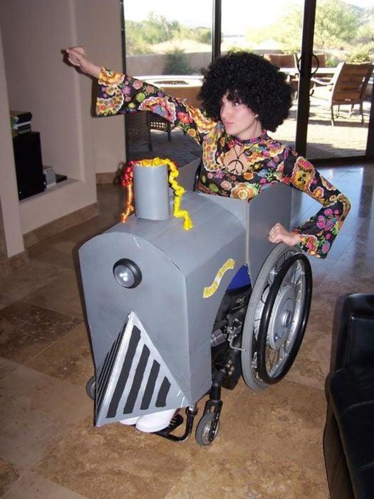 persona disfrazada de funky en silla de ruedas decorada como locomotora