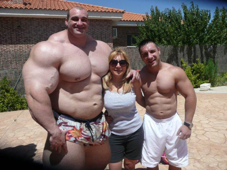 mujer con dos fisicoculturistas