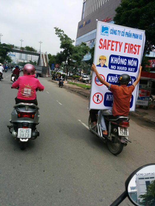hombre de copiloto de moto cargando un enorme cartel