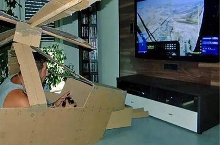 hombre jugando videojuegos en un avión de cartón
