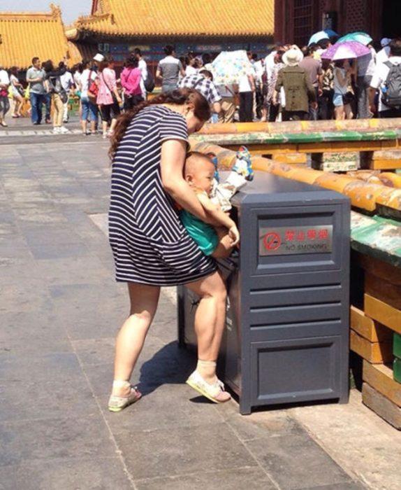 señora con bebé en el bote de basura