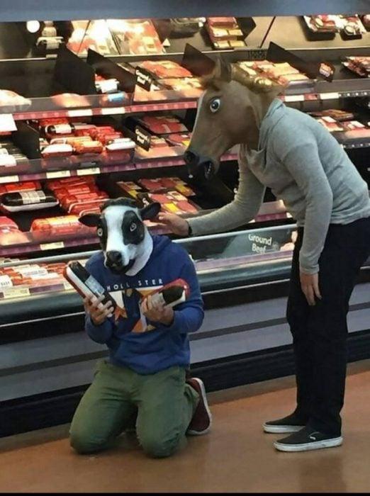 dos jovenes con máscaras de animales se lamentan en la sección de carnes frías de centro comercial