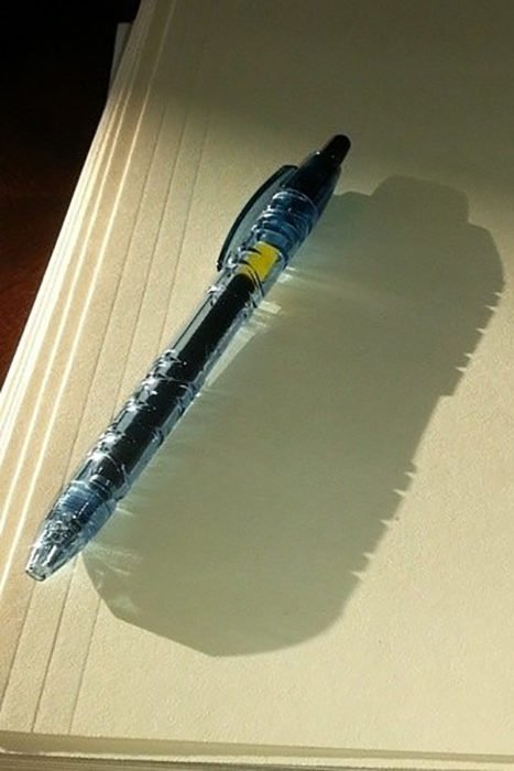 bolígrafo cuya sombra proyecta una botella