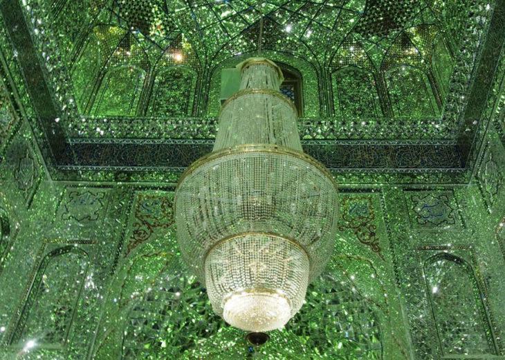 techo con cristales verdes del que cuelga un candelabro