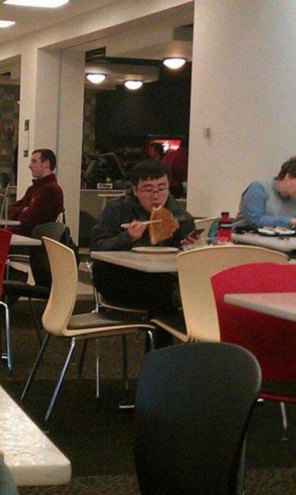 muchacho comiendo pizza con palillos