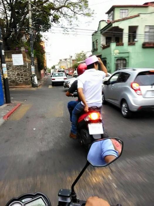 chico en moto con recipiente en la cabeza