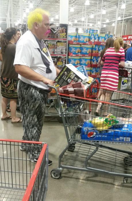 hombre con cabello amarillo y bigote rosa empuja carrito de compras