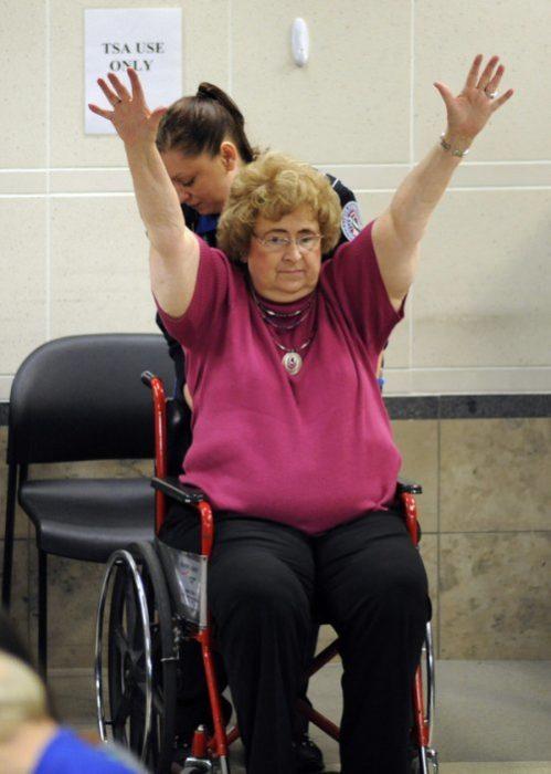 señora en silla de ruedas con las manos arriba pasando punto de revisión en el aeropuerto