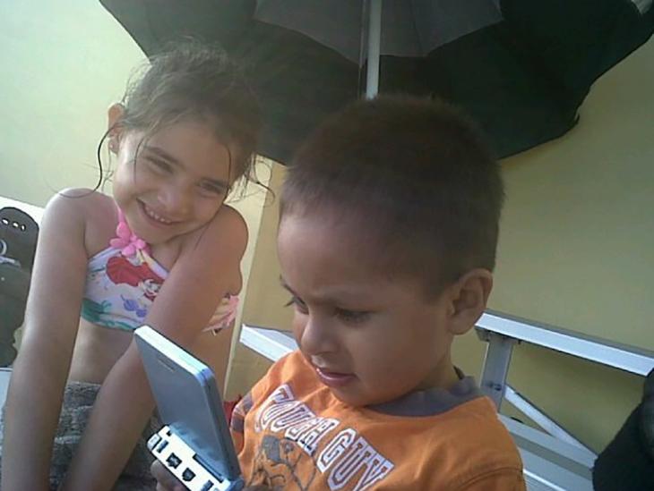 niña mirando tiernamente a un niño que juega videojuegos