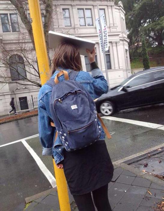 muchacha tapándose de la lluvia con una laptop