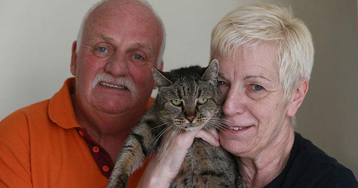 Pareja sosteniendo a un gato para la foto