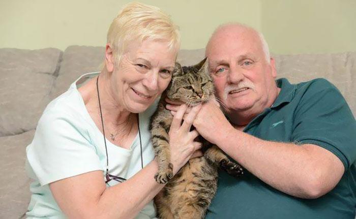 Dueños abrazando as u gato