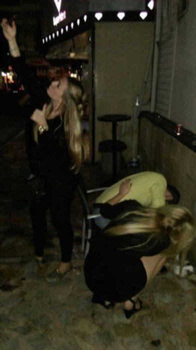 2 Tipos de chicas - una tomando selfie y otra ayudando a su amigo borracho