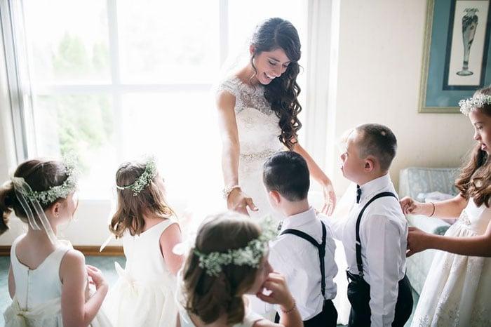 Maestra en su vestido de novia jugando con sus alumnos