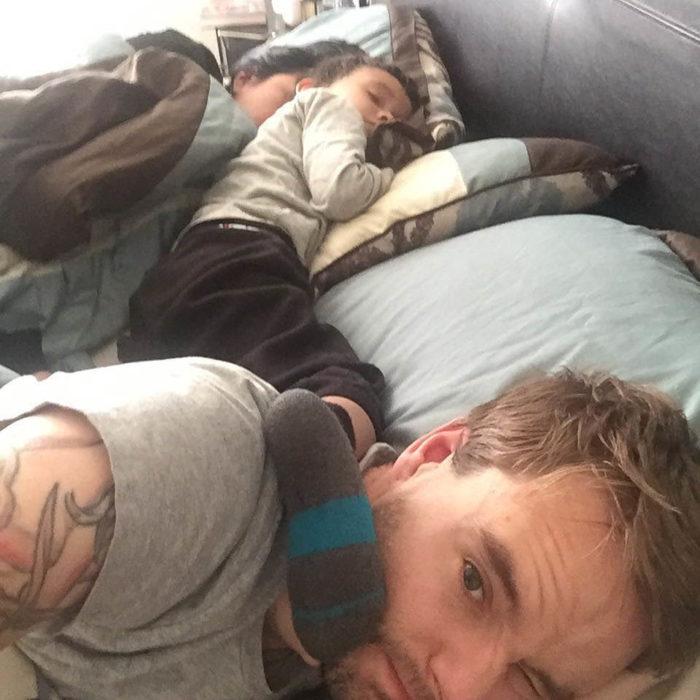 Papás cansados - bebé dormido con sus papás en la cama