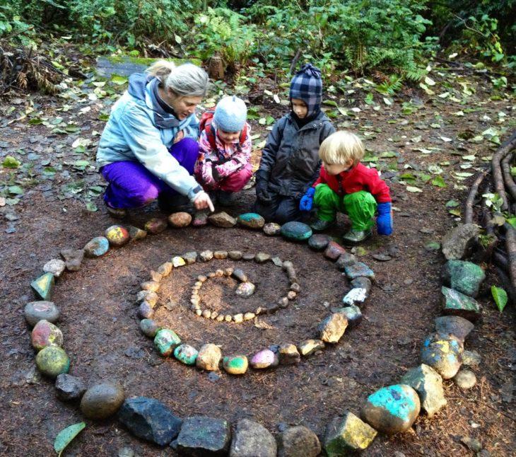 niños en bosque poniendo piedras en espiral