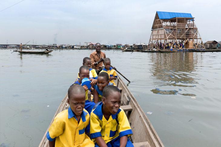 niños en lancha se dirigen a escuela flotante de makoko