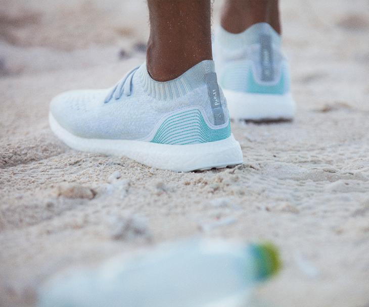 hombre usando tenis azules en arena de mar