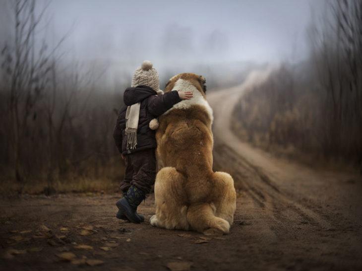niño y perro dando la espalda en un paisaje