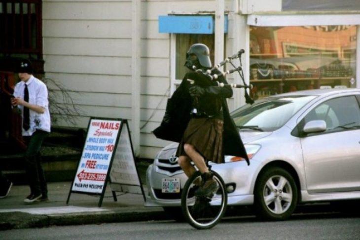 hombre en monociclo con falda escocesa y casco de darth vader
