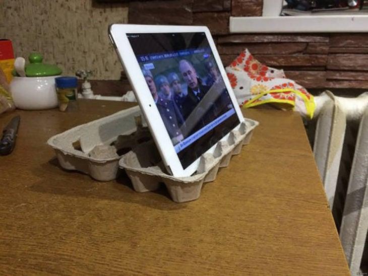 tablet sostenida por cartera de huevos