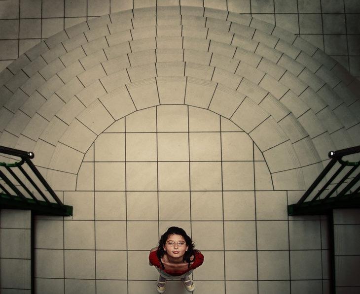 niña mirando al cielo sobre escaleras geométricas