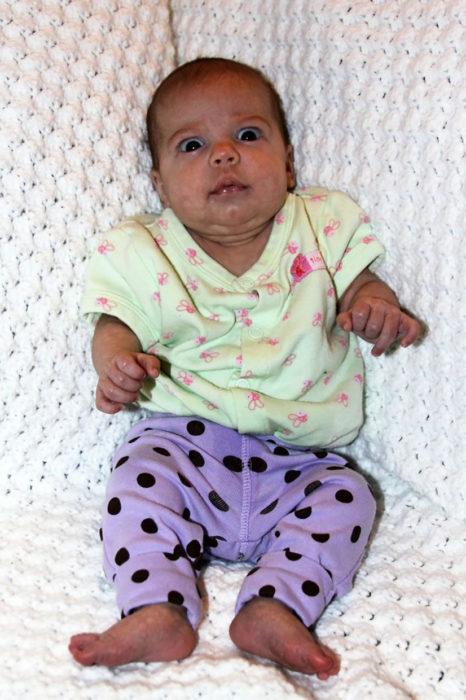bebé con pantalones lilas de lunares y blusa verde