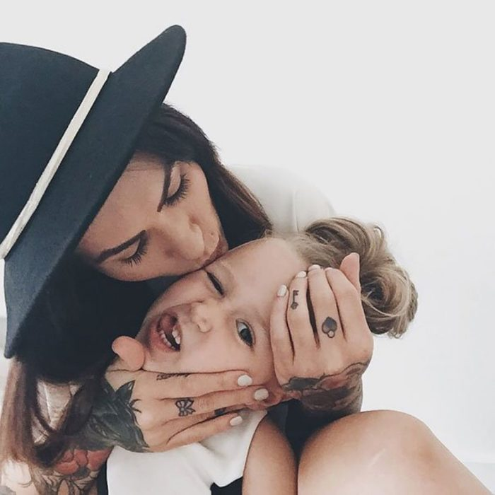 mamá tatuada besando a su hijo