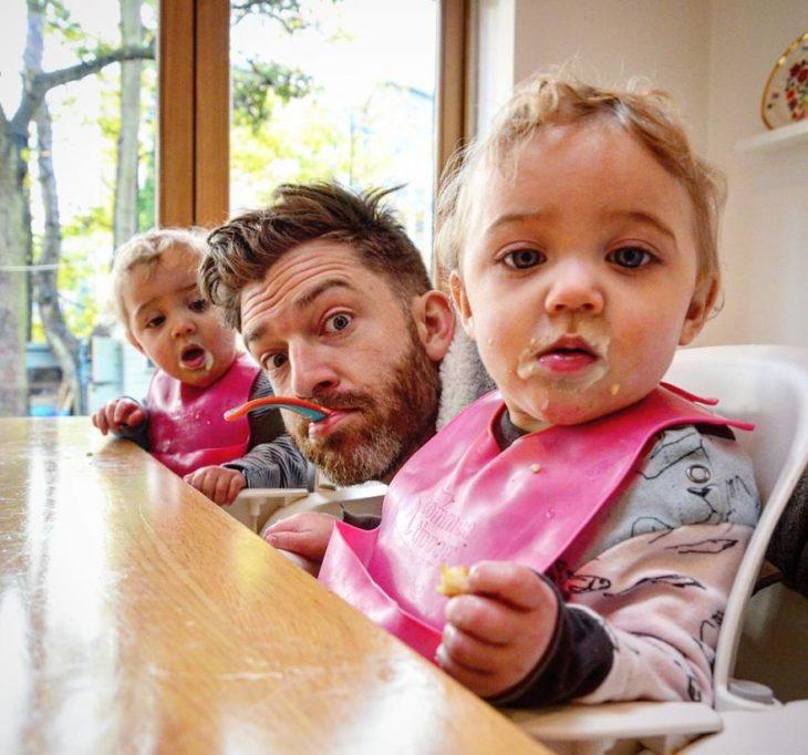 papá con gemelas bebés sentados a la mesa
