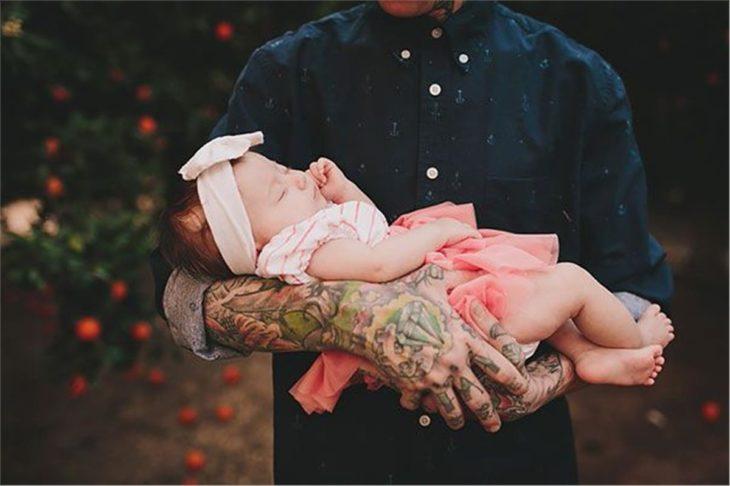 brazos de hombre tatuado cargan a una niña