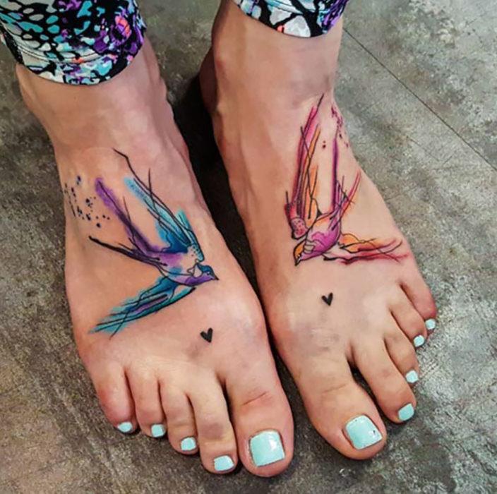 tatuaje estilo acuarela de aves en los pies de una mujer
