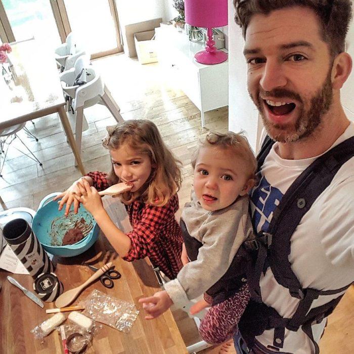papá sostieniendo a bebé mientras hija prueba mezcla de pastel