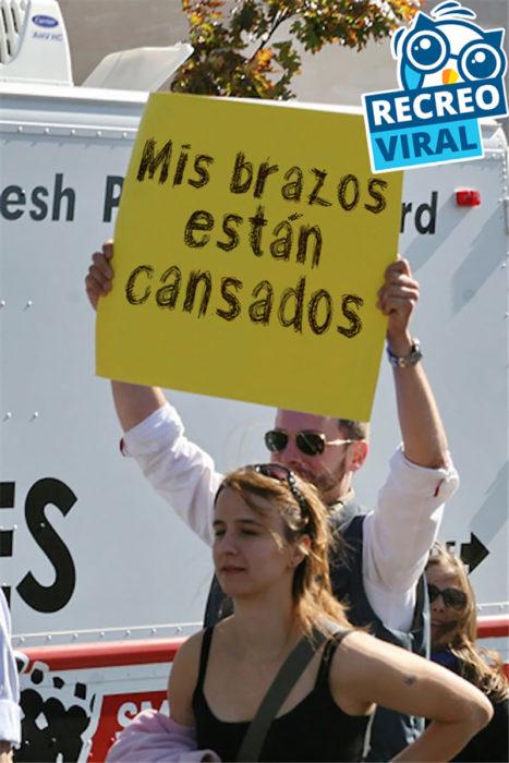 hombre sosteniendo un cartel amarillo