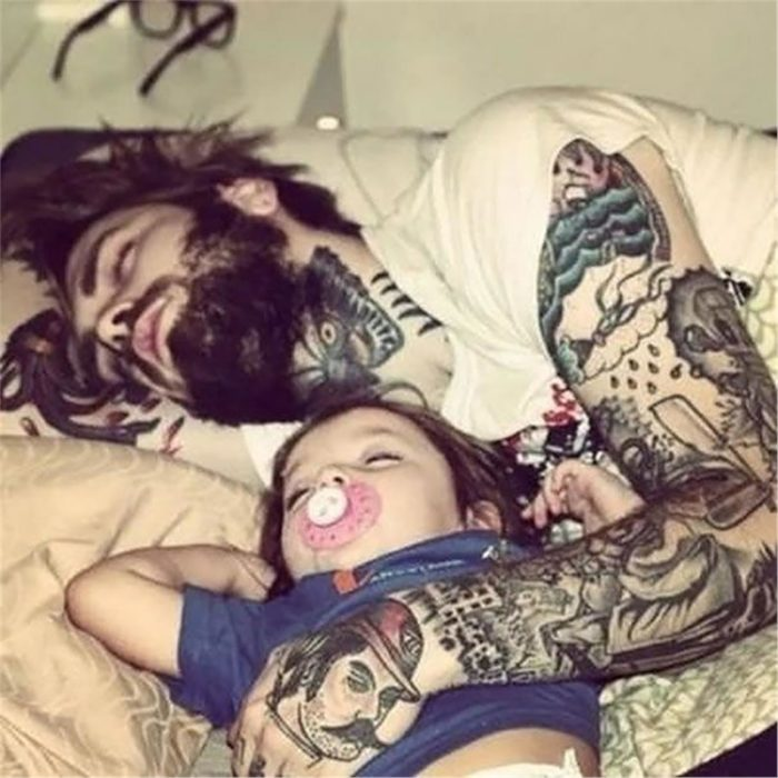 hombre con barba y tatuajes durmiendo al lado de su hijo pequeño