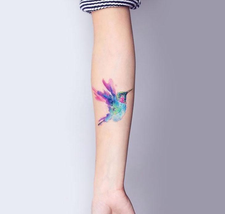 tatuaje de colibrí estilo acuarela en los brazos de una mujer