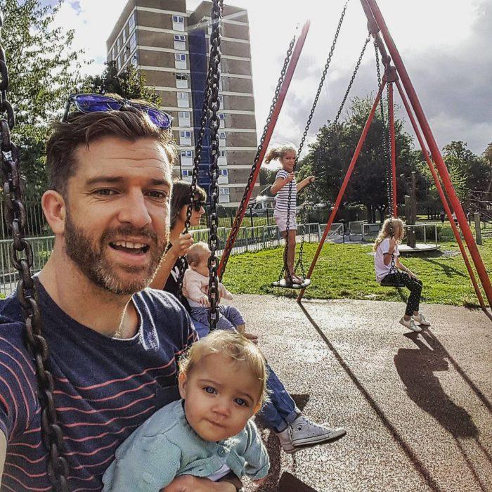 papá con sus hijas en los columpios
