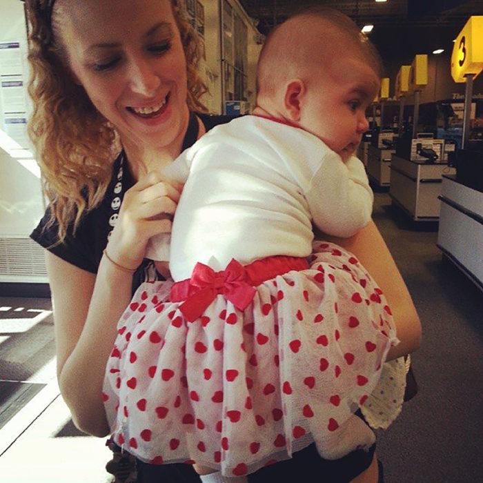 señora cargando a bebé con vestido de bolitas y moño