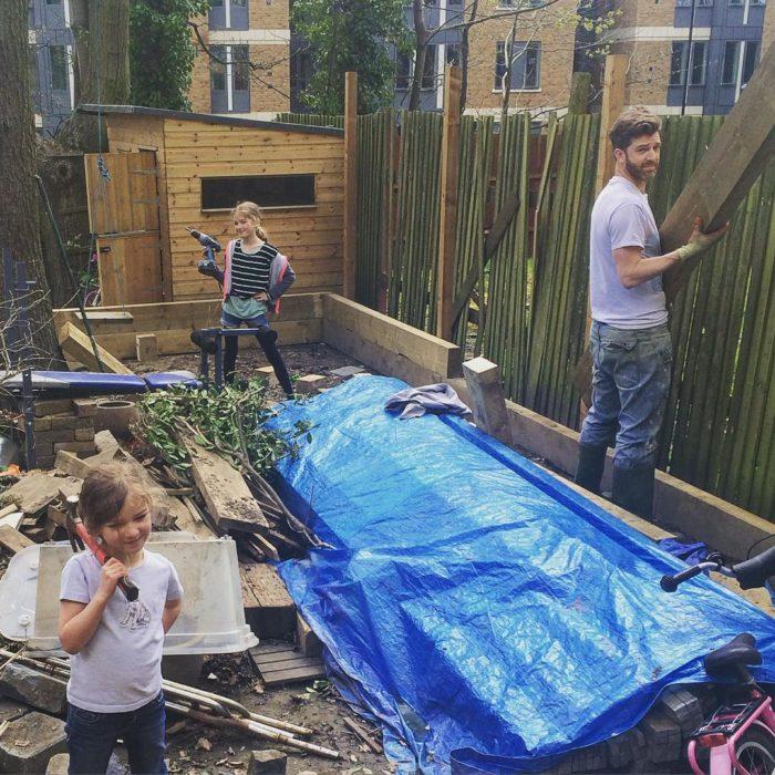 hombre haciendo trabajso en el jardín con sus dos hijas