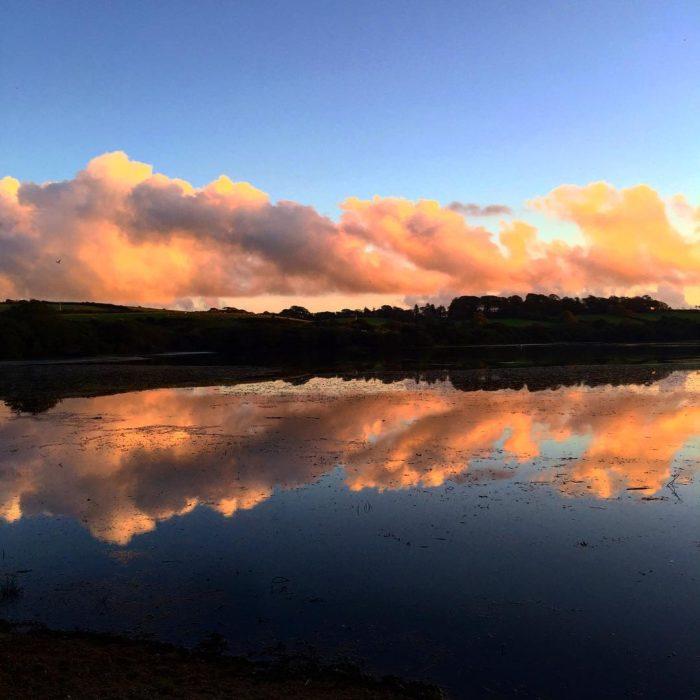 paisaje de montaña y cielo se refleja simétricamente en el agua