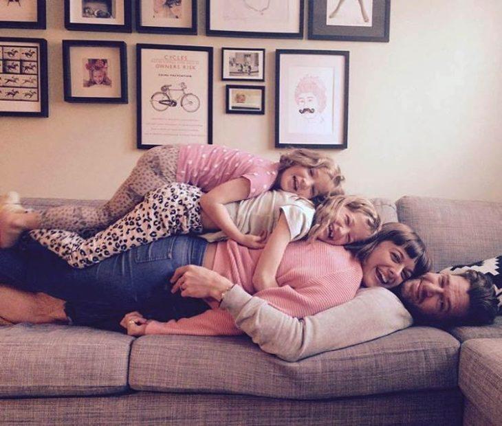 cuatro hijas recostadas sobre su papá
