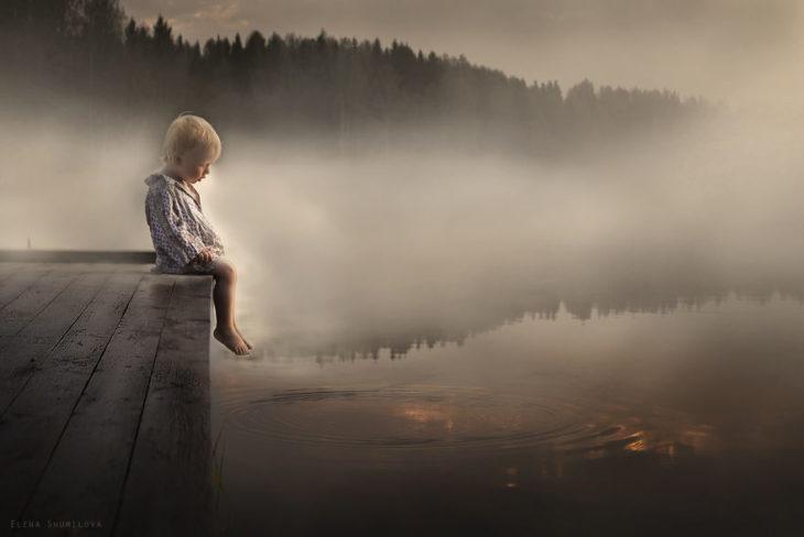 niño sentado al lado de un lago