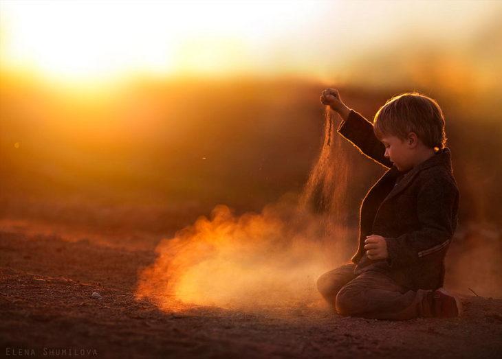 niño jugando con polvo en un atardecer