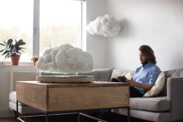 chico en un sala con una bocina levitante en forma de nube