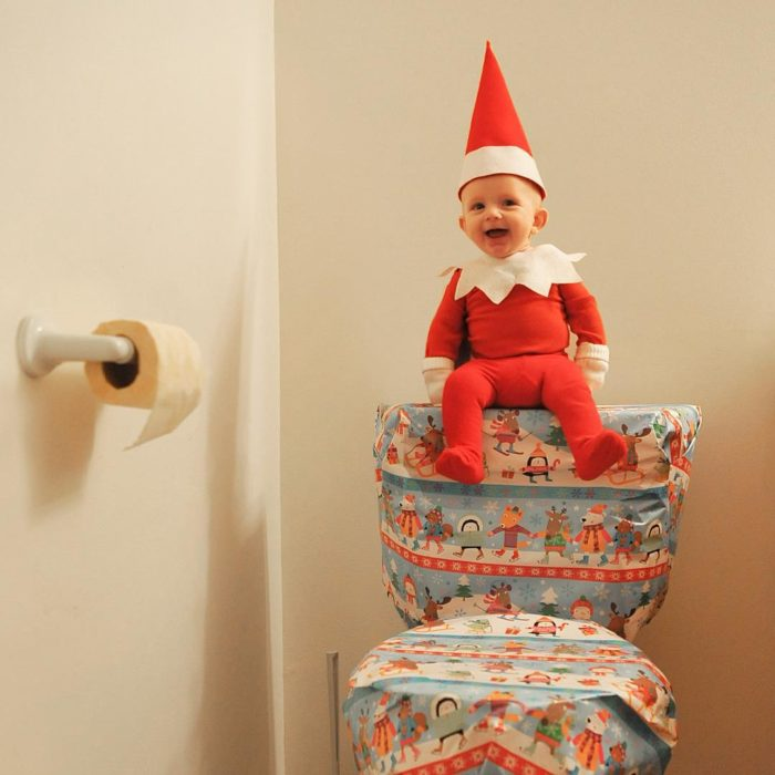 bebé vestido de elfo sobre un inodoro
