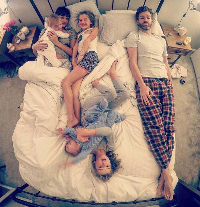 familia de esposo, esposa y cuatro hijas en la cama