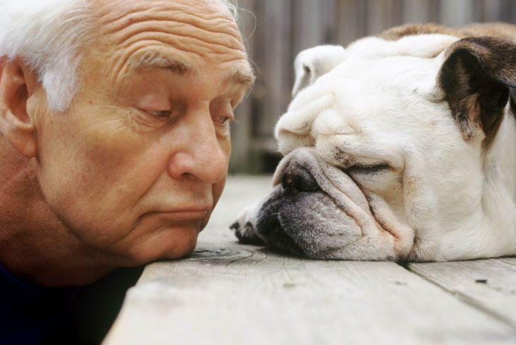 anciano levantando una ceja a un perro