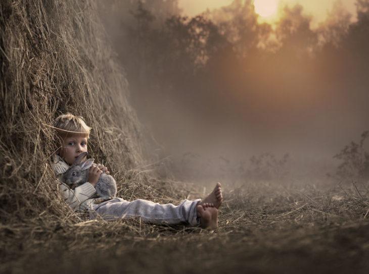 niño recostado en árbol sosteniendo un conejo
