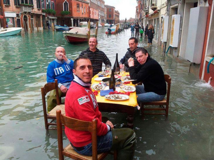 amigos comiendo en un lugar inundado